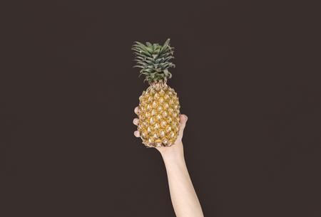 Menselijke hand met ananas fruitvoeding