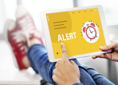 hands with illustration of alarm clock notification for important appointment on digital tablet