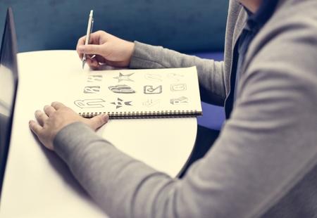 ドリュー ブランド ロゴ創造的なデザインのアイデア ノートを持っている手