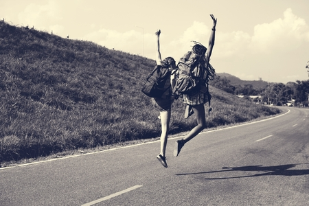 Diverse Backpacker Women Jumping on The Street
