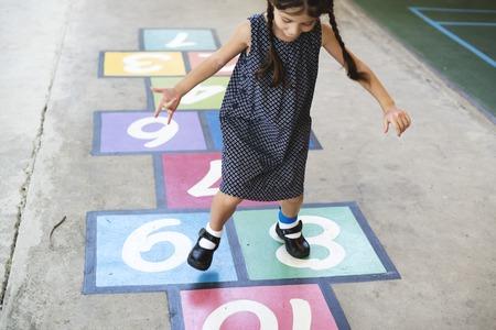 Junges Mädchen spielt Hopscotch Standard-Bild - 82419578