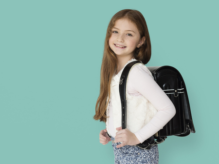 Young freckled girl carrying a backpack smiling portrait Stock Photo