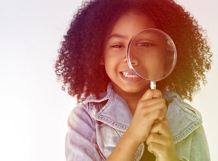 虫眼鏡を使用して探索する子供
