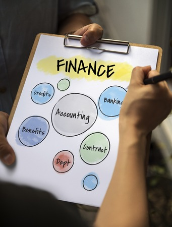 Person signing on a clipboard with finance concept