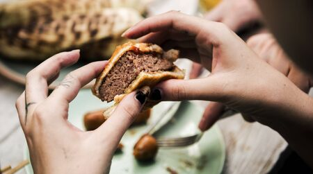 Clsoeup of hands holding bite burger Banco de Imagens