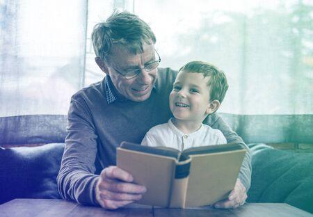 Großvater und kleiner netter Enkel , der zusammen liest Standard-Bild - 82397887