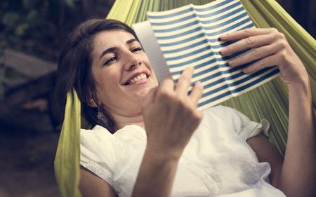 Woman lying on hammock chilling reading book 版權商用圖片