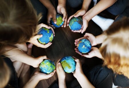 Group of diverse kids hands holding cupping globe balls together Banco de Imagens