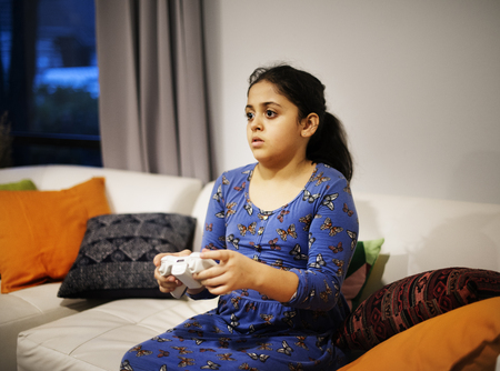 Little girl playing video game in living room