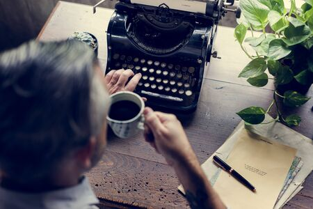 Man drinking coffee with vintage typewriter