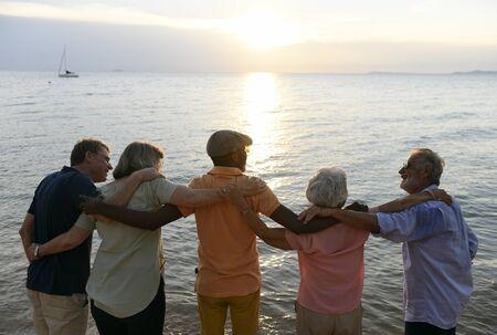 Group of senior friends arm around on the beach