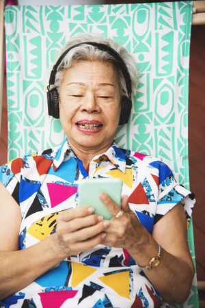 Senior adult woman lay down on beach chair and listening to music