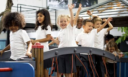 Group of diverse kindergarten students with arms raised Imagens