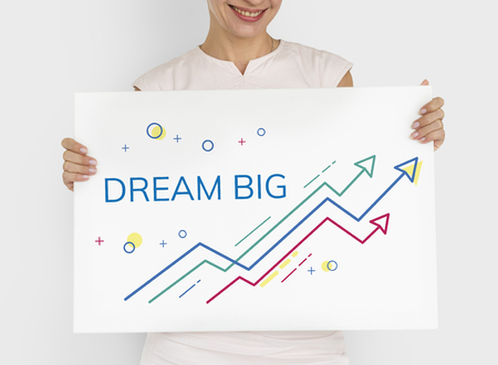 Woman holding card with phrase Dream Big