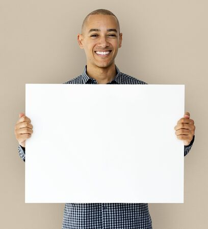 A guy is smiling with placard