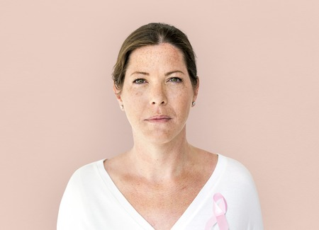 Woman with pink ribbon for breast cancer awareness charity studio portrait Zdjęcie Seryjne