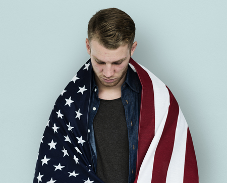 Man close up holding flag around shoulder posing for photoshoot 版權商用圖片