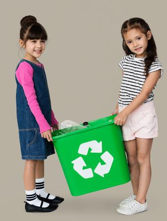 niños reciclando: Two girls are holding a recycle bin Foto de archivo