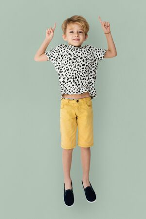 Young blonde boy jumping mid-air portrait Stock Photo