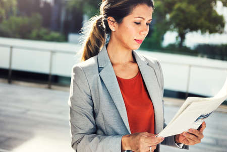 information analysis: Businesswoman Reading Newspaper Information City Concept