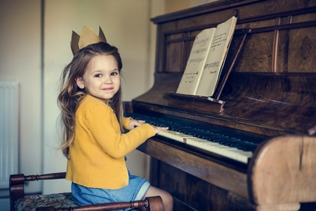 Adorable Cute Girl Playing Piano Concept Imagens