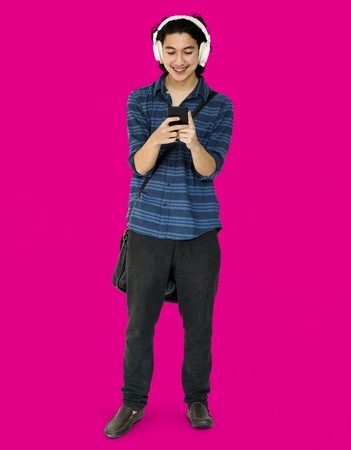 techie: Young man full boady listening music on smart phone Stock Photo