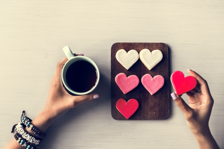 People Hands Showing Heart Shape Cookies with Coffee Cup