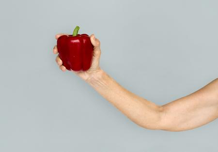Hand met rode paprika