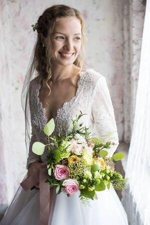 꽃 꽃다발을 들고 매력적인 아름다운 신부