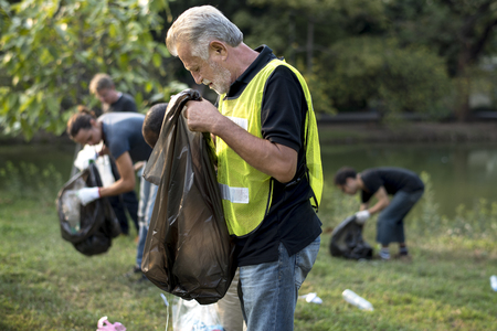 人々 の多様なグループは、パーク ボランティアのコミュニティ サービスのゴミを拾う 写真素材