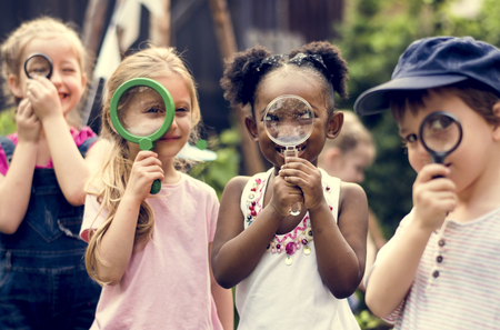 Group of kindergarten kids friends holding magnifying glass for explore
