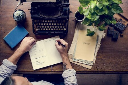 Man writing on notebook and vintage typewriter Stock Photo