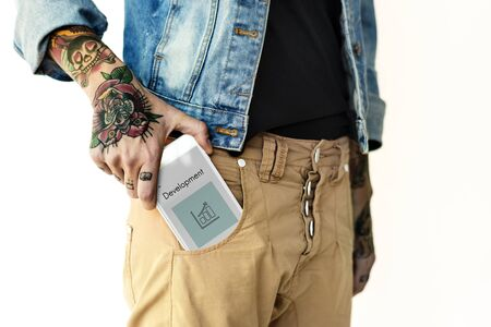 Hand holding network graphic overlay digital device in trouser pocket