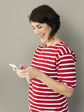 Adult Woman Using Mobile Phone Cheerfully Фото со стока