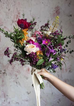 Mano di Peopl che tiene il mazzo di bei fiori Archivio Fotografico - 82939807