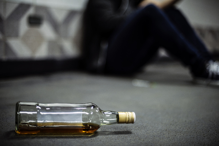 Liquor Alcohol Bottle Lying on The Floor Stock Photo