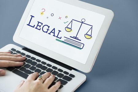 Hands using laptop with scale icon and legal court word concept Stock Photo