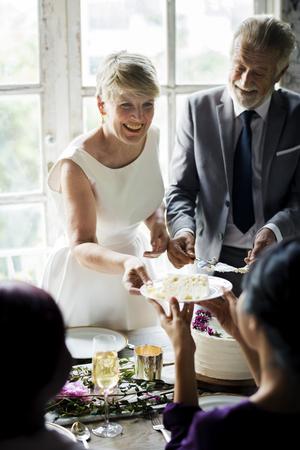 Senior Woman Handing Cake to Friend