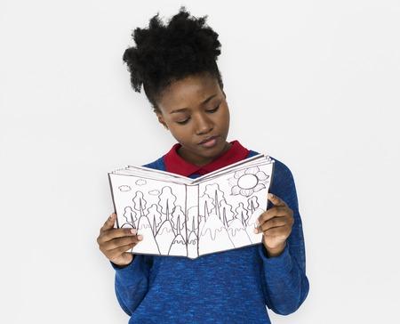 Una niña paga atención leyendo un libro Foto de archivo - 83023784