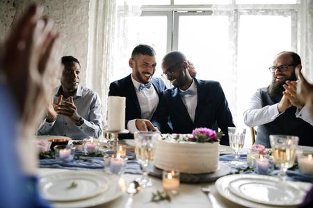 同性カップル結婚式のケーキカットを手します。
