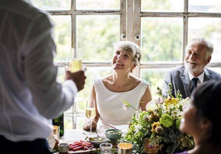 Senior paar zitten vrolijk bij de receptie van het huwelijk Stockfoto