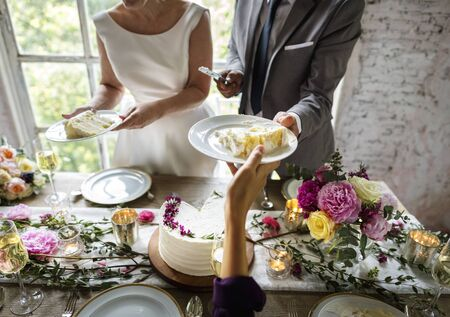 Hands Giving Cut Wedding Cake to Guess Stock Photo