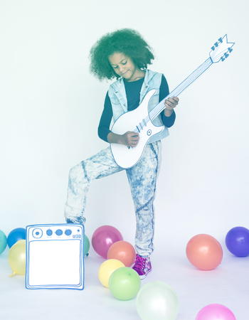 Child standing and playing electric guitar