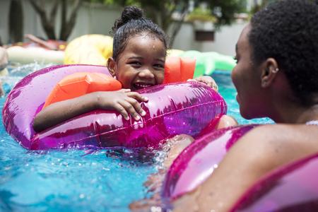Primer plano de madre negra e hija disfrutando de la piscina con tubos inflables Foto de archivo - 83008425