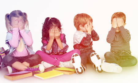 Group of little kids playing peek-a-boo together Imagens