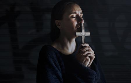 Manos de mujer adulta con Cruz orando por Dios Religión Foto de archivo - 82955548