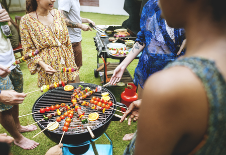 Group of diverse friends grilling barbecue outdoors Zdjęcie Seryjne