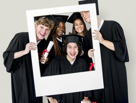 모자와 가운을 쓰고있는 다양한 학생 포토 프레임 스튜디오 초상화를 들고 스톡 콘텐츠