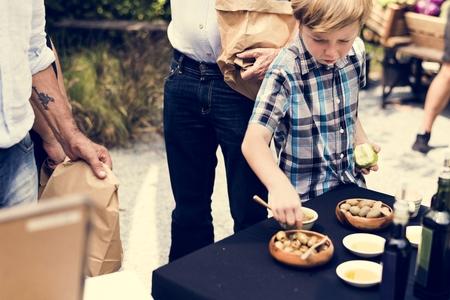 Little Boy Testing Preserve Olive Sample at Market
