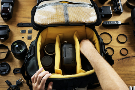 Hands holding a camera bag preparing put an equipment in